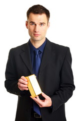 Handsome businessman in suit standing holds gold brick