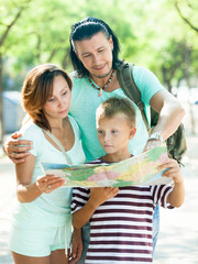 couple with son looking  the map