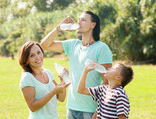 family of three drinking from plastic bottles
