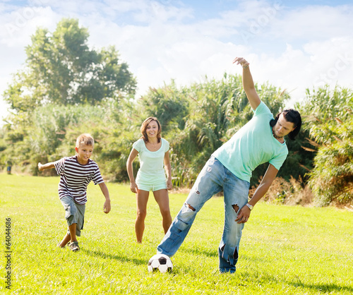 Happy family with teenager  playing in soccer