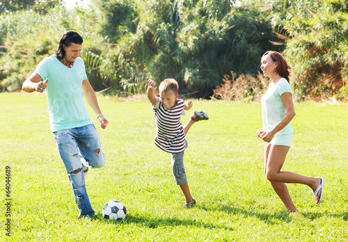 Middle-aged couple and teenager playing with  ball