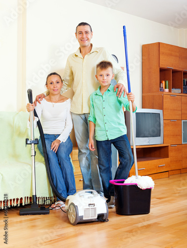 Portrait of happy family  with  cleaning equipment