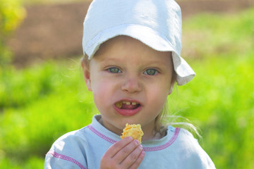 portrait small child in a cap eating cookies