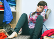 красивая молодая женщина сидит среди разбросанной одежды