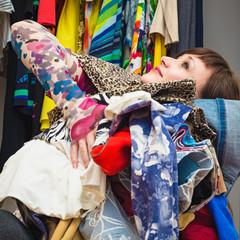 молодая привлекательная женщина с охапкой одежды в руках