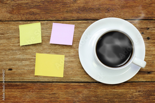 sticker note and a cup of coffee on wood table