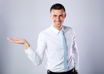 Happy handsome businessman showing empty hand on gray background