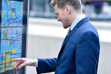 Businessman checking a bus timetable