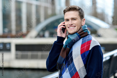 Handsome man using mobile at bridge railing