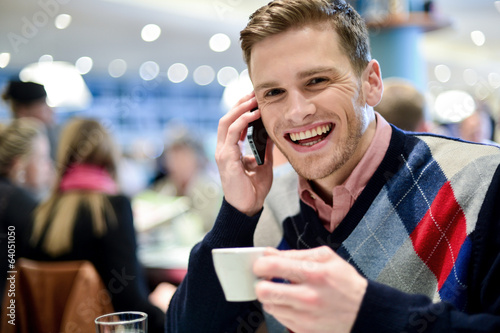 Young man using mobile phone in cafe