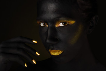 Beautiful dark face isolated on black with gold make up