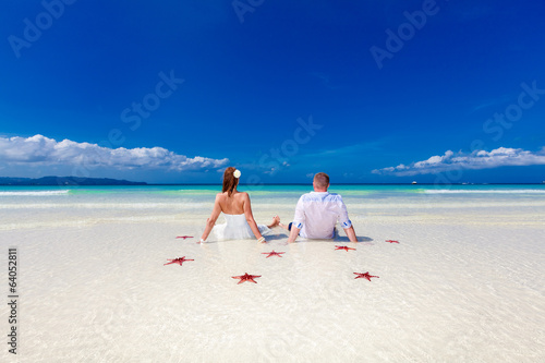 Bride and Groom jumping on tropical beach shore with red starfis