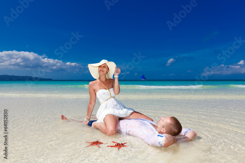 Bride and Groom on tropical beach shore with red starfish in the