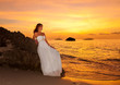 the bride on a tropical beach with the sunset in the background