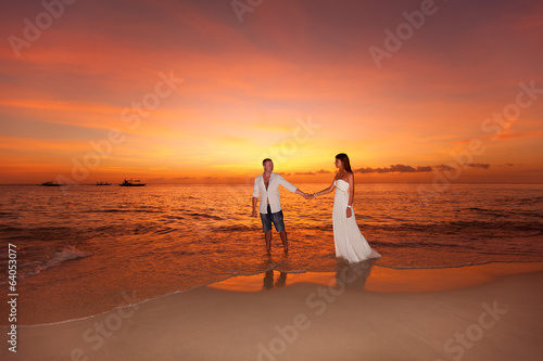 bride and groom on a tropical beach with the sunset in the backg