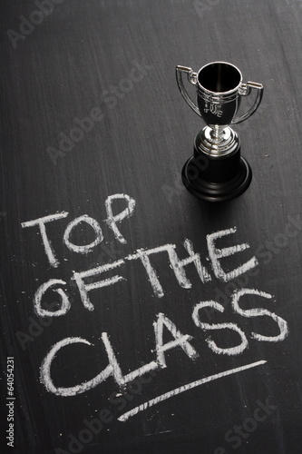 Top of the class on a blackboard with a silver trophy cup
