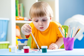 kid painting at table in children room