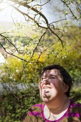 behinderte Frau unter einem Zwetschgenbaum im Sonnenschein
