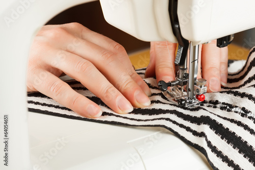 doing some sewing clothings from fabric on a sewing typewriter