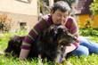 Portrait einer behinderten Frau mit Hund auf einer Wiese