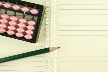 Abacus put on notebook with pencil