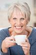 lächelnde ältere frau genießt eine tasse kaffee