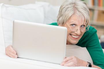 lächelnde rentnerin mit laptop