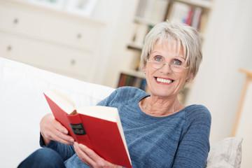 entspannte ältere frau liest ein buch