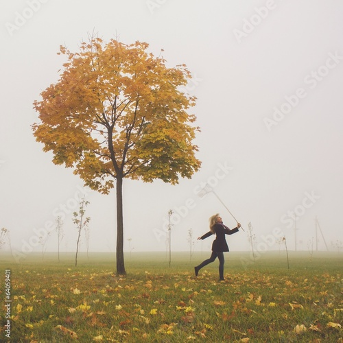 girl trying to catch leaf with net