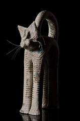 Cat figurine on black background