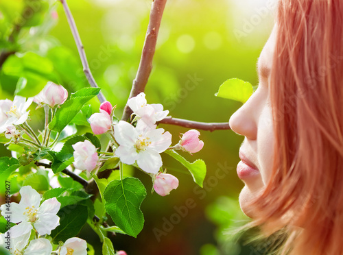 young girl smelling blossoms