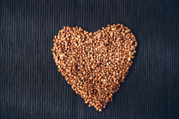 Heart shaped buckwheat cereals on a black linen serviette