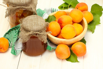 canned apricots and jam in a jars and ripe apricots in bowl