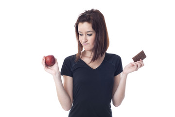 Worried woman torn between a chocolate bar and fresh apple