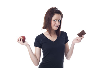 Young woman torn between chocolate bar and fresh apple
