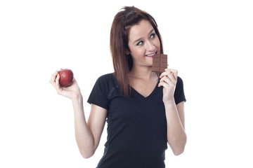 Young woman biting a chocolate bar and catching a fresh apple