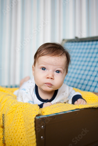 A cute baby lying on yellow knitted wrap