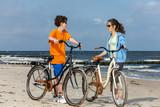 Teenage girl and boy biking on beach