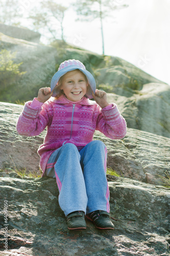 Happy girl on a rock.