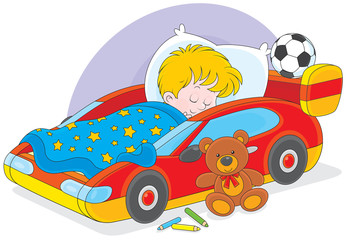 Little boy sleeps in his bed made as a sport car