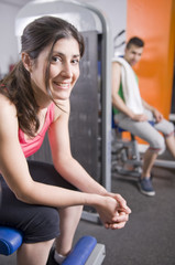 Two persons relaxing at gym on machines