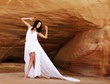 woman in white dress dancing on the desert