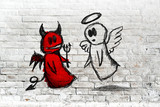 Angel and devil fighting; doodle drawing on white brick wall