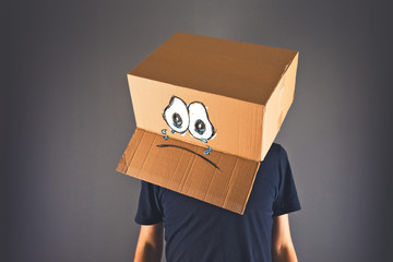 Man with cardboard box on his head and sad face expression