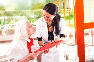 senior woman with a nurse looking at medical report