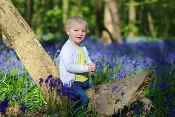 Lovely toddler girl plays in beautiful forest full of bluebells