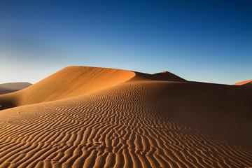 Tracks of wind on an orange sand dune
