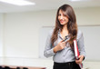 Smiling teacher standing in front of blackboard