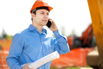 Engineer talking at the phone in a construction site