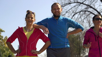 Happy sporty joggers, couple standing in park